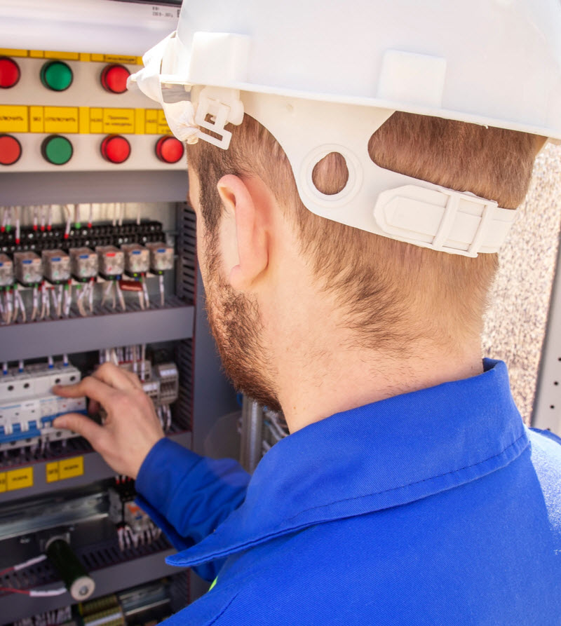 Engineer in helmet is testing electrical equipment