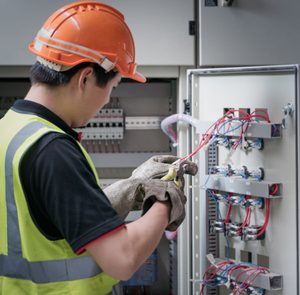 Electrician working with wires in the control room