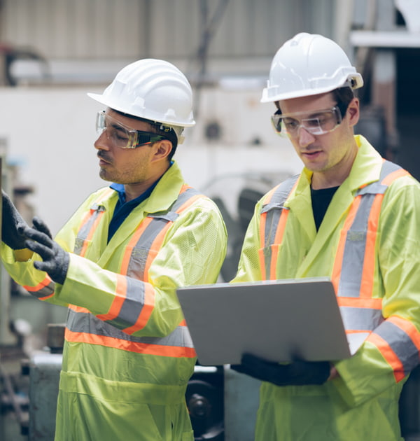 Technician engineer and mentor checking process on laptop