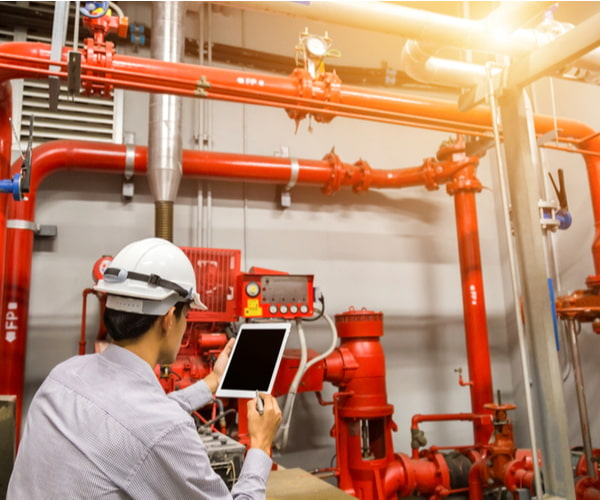 Engineer with tablet check red generator pump