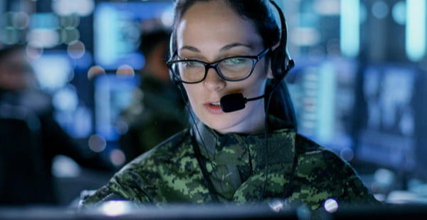 Female army officer using computer in headphones