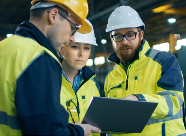Industrial engineers talk with factory worker while using laptop